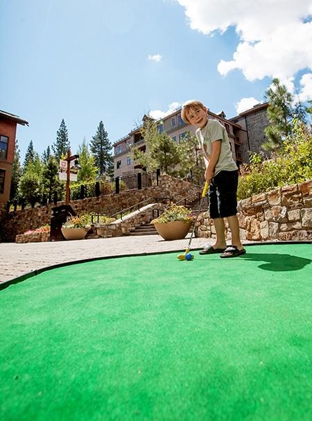 child playing mini golf